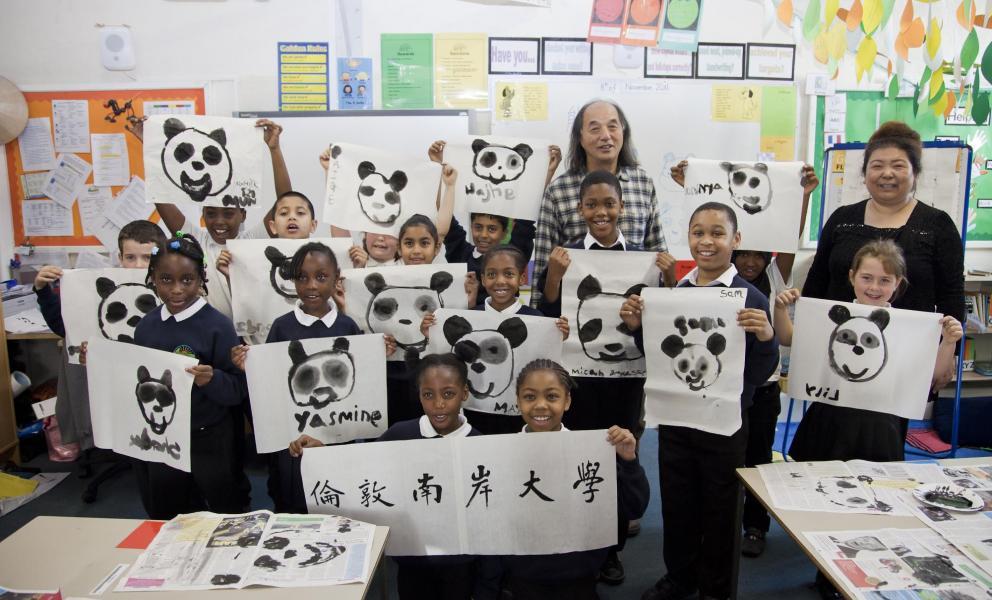 class holding up artwork