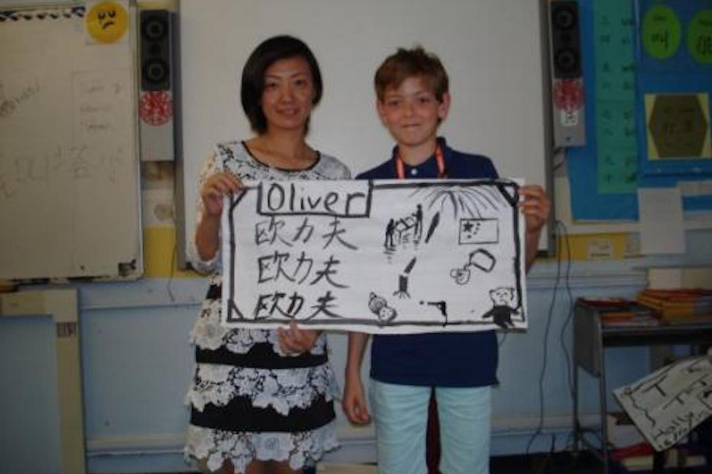 A student showing off his Chinese name that he wrote