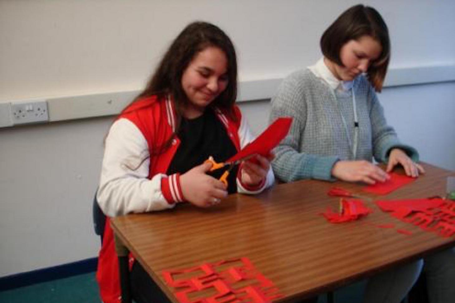 Students carefully cutting out the Chinese character of Xi (meaning 'Happiness')
