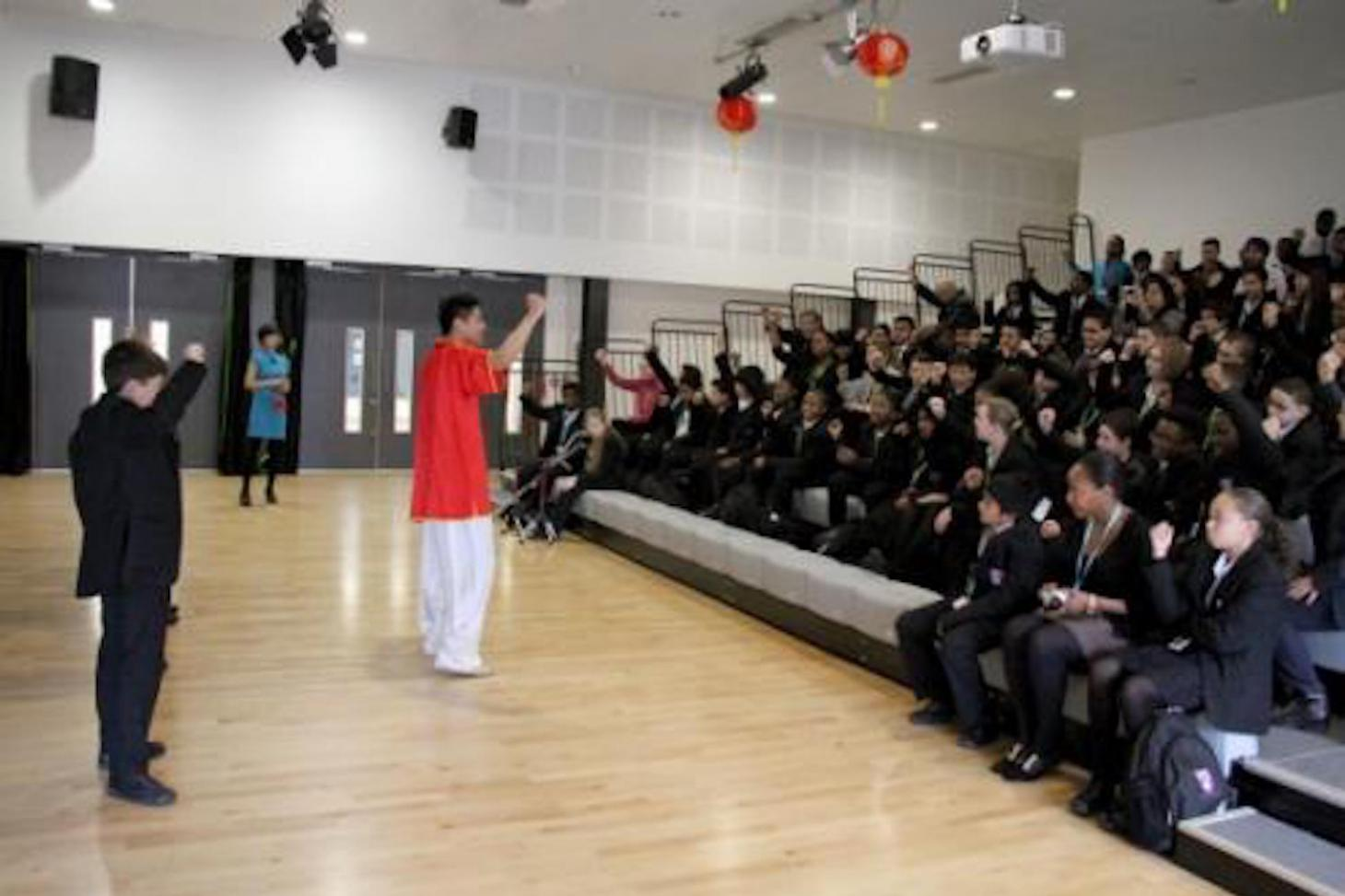 The audience learning the Chinese martial arts greeting